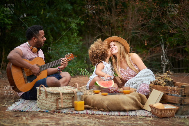 Happy young mixed race parents with cute curly haired daughter playing guitar and laughing while chilling together during picnic in summer day in green forest