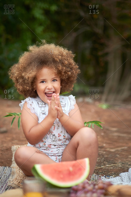 Cheerful little curly haired girl clapping hands and looking at camera while sitting near piece of ripe red watermelon during picnic in summer day