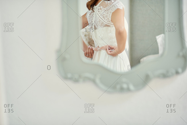Back view of anonymous bride tying bow on elegant wedding dress while reflecting in mirror and  standing at home