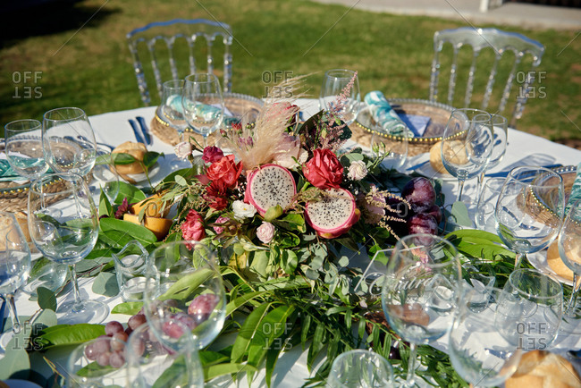 Round table with various fruits and flowers surrounded by chairs and placed in garden for wedding celebration