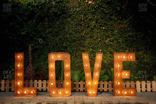 Installation of wooden letters with light bulbs placed in courtyard in evening during wedding celebration