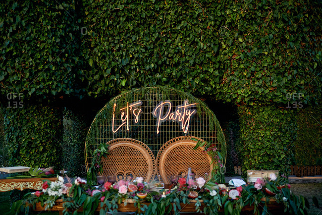 Wicker chairs for bride and groom with illuminated sign lets party placed in green garden for wedding celebration in summer