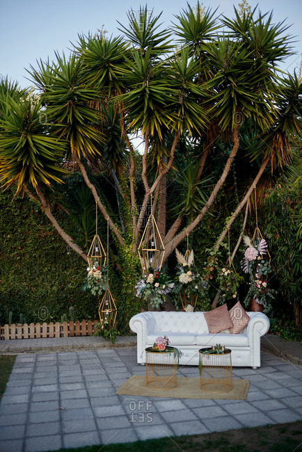 Luxury leather couch and tables placed under tropical trees in backyard in evening