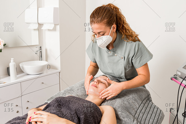 Professional beautician doctor in protective mask applying facial cream on woman while preparing for dermatology procedure in modern salon