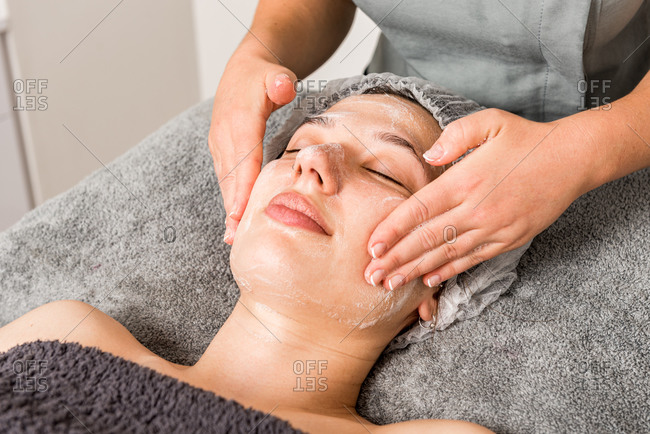 Cropped unrecognizable professional beautician doctor applying facial cream on woman while preparing for dermatology procedure in modern salon