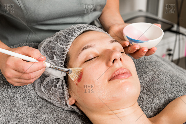 Cropped unrecognizable female beauty specialist in uniform spreading mask on face of relaxed client while working in modern salon