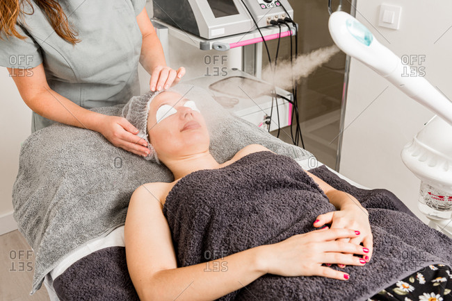 Cropped unrecognizable professional beauty therapist using facial steamer for cleaning treatment of female client in contemporary cosmetology clinic