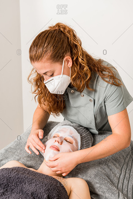 Cosmetician in protective mask applying facial cloth mask on female client during rejuvenate skincare procedure in modern beauty salon