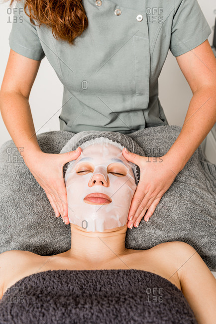 Crop anonymous cosmetician applying facial cloth mask on female client during rejuvenate skincare procedure in modern beauty salon