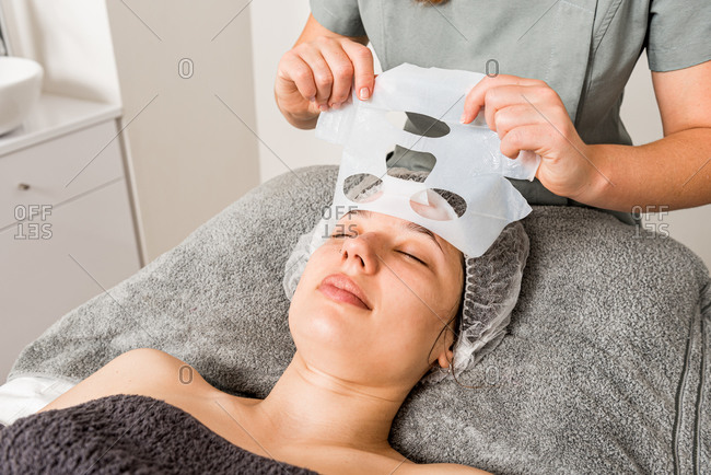 Crop unrecognizable beautician removing moisturizing cloth mask from face of relaxed female client during professional treatment in modern clinic