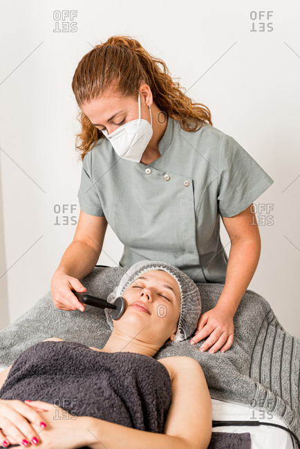 Relaxed female client getting skincare facial massage with ultrasound device from professional cosmetician in protective face mask in contemporary beauty clinic