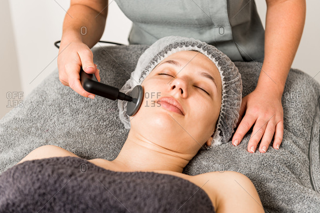 Relaxed female client getting skincare facial massage with ultrasound device from cropped unrecognizable professional cosmetician in contemporary beauty clinic