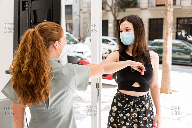 Professional staff in uniform and protective mask greeting female patient with gesture in entrance of modern spa salon during coronavirus pandemic