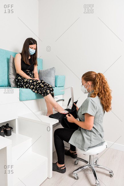 Young female client in protective mask sitting on chair and getting pedicure treatment from professional artist in modern beauty salon