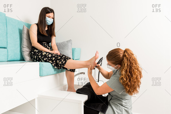 Side view of professional pedicure specialist polishing foot of female customer in protective mask with machine tool during appointment in modern apparatus cosmetology center