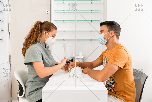 Side view of young male in protective mask getting professional manicure procedure from female specialist in modern beauty center