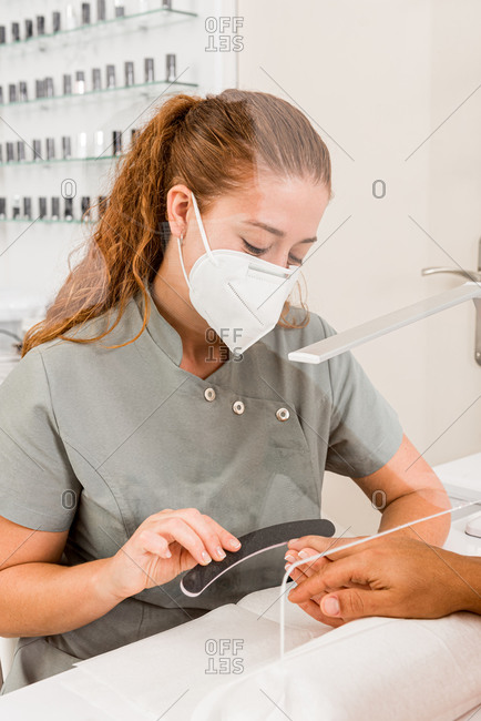 Side view of young female specialist in protective mask doing professional manicure procedure in cropped unrecognizable male in modern beauty center