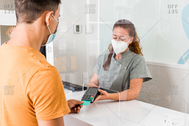 Young female specialist in protective mask holding card reader while male patient paying for treatment with credit card in modern clinic