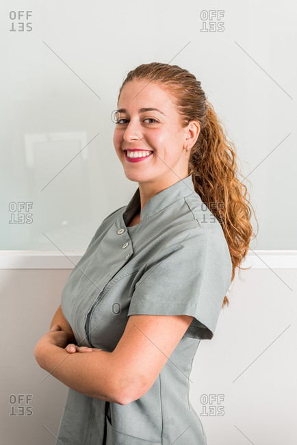 Side view of positive young female specialist of modern beauty salon in gray uniform looking at camera and smiling friendly