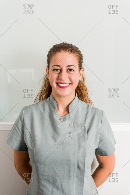 Positive young female specialist of modern beauty salon in gray uniform looking at camera and smiling friendly