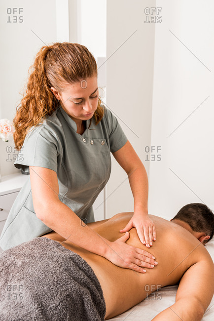 Professional female therapist doing massage on back of male client in modern clinic