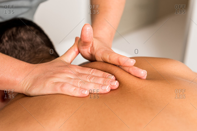 Cropped unrecognizable professional female therapist doing massage on back of male client in modern clinic