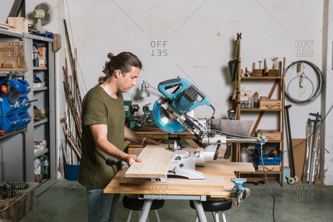 Side view of male carpenter cutting wooden plank with miter saw while working in bright workshop