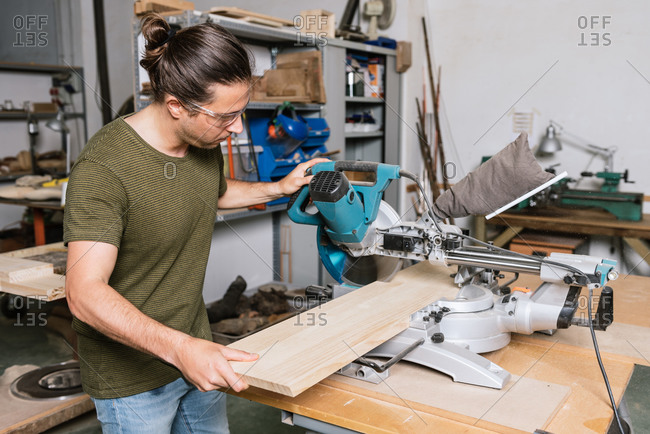 Side view of male carpenter in protective goggles cutting wooden plank with miter saw while working in bright workshop