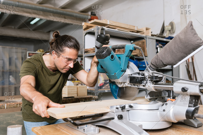 Male carpenter in protective goggles cutting wooden plank with miter saw while working in bright workshop