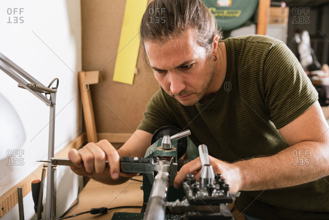 Handsome male woodworker standing at workbench and measuring detail with caliper tool while working in workshop