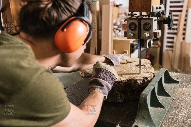 Male carpenter in protective ear muffs and goggles cutting piece of wood with band saw in shabby workshop