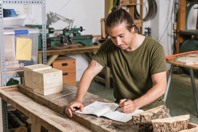 Concentrated male carpenter standing at workbench and taking notes in notebook while working in garage