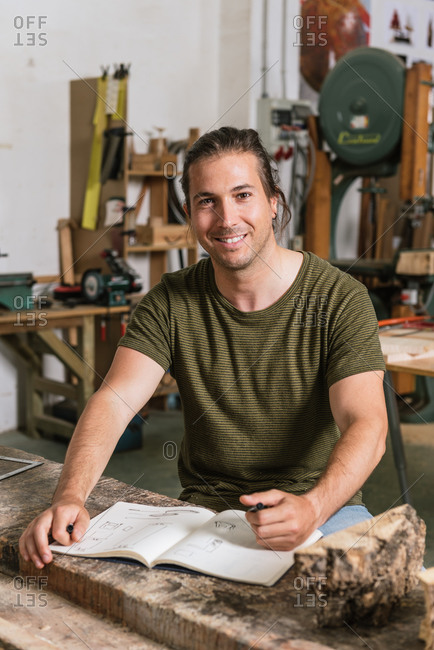 Cheerful male carpenter standing at workbench and taking notes in notebook while working in garage