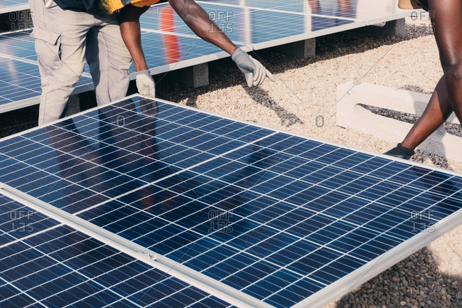 Cropped unrecognizable busy black male engineers installing solar batteries in construction site of modern factory during sunny day