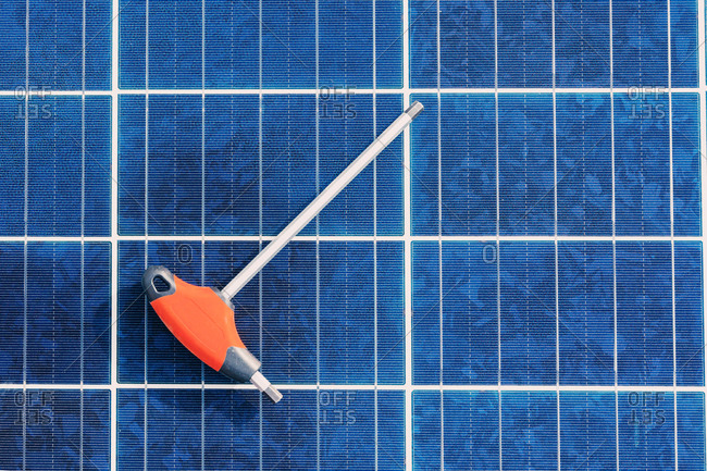 Screwdriver placed on top of contemporary solar battery at factory