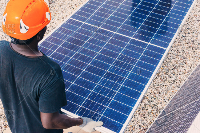 Back view of unrecognizable African American worker walking with solar panel on sunny day in industrial area