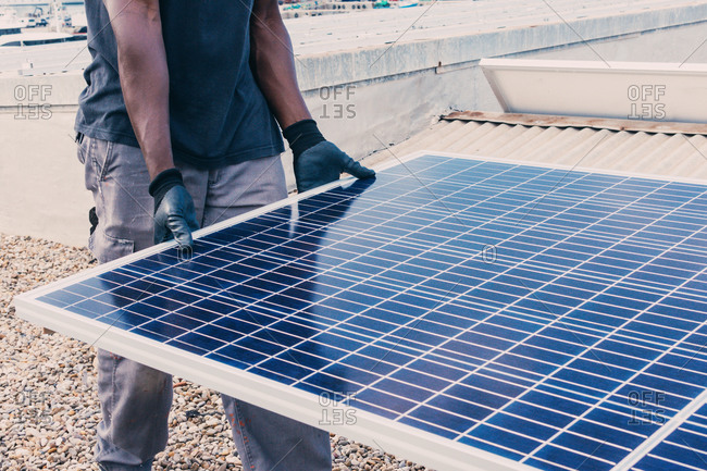 Crop unrecognizable African American worker walking with solar panel on sunny day in industrial area
