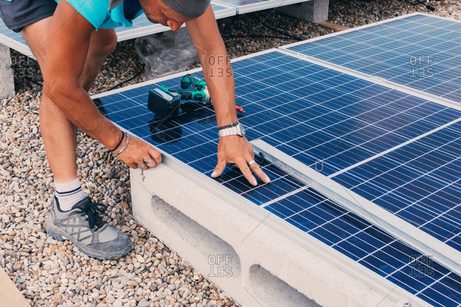 Anonymous male engineer using electric screwdriver and installing contemporary solar battery at factory