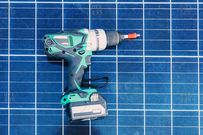 Electric screwdriver placed on top of contemporary solar battery at factory