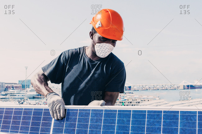 Black workman in helmet and protective mask installing solar battery in industrial area of contemporary plant