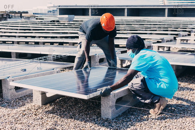 Busy black male engineers installing solar batteries in construction site of modern factory during sunny day