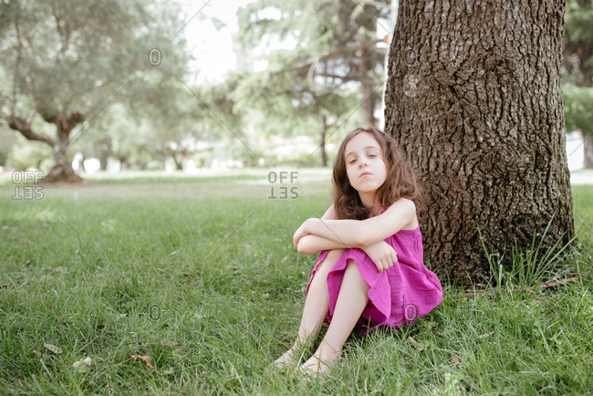 Full body of tranquil little girl in pink dress sitting on green grass near tree trunk while resting in park in summer day