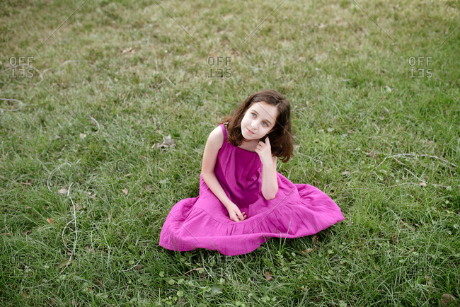 Adorable thoughtful preteen girl with curly hair wearing pink summer dress sitting on green meadow in summer park