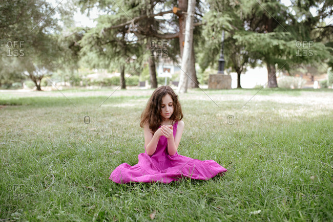 Adorable tranquil preteen girl with curly hair wearing pink summer dress holding green sprig while sitting on green meadow in summer park