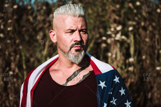 Serious middle aged bearded male with tattoo wrapped in American flag looking away while standing against blurred nature