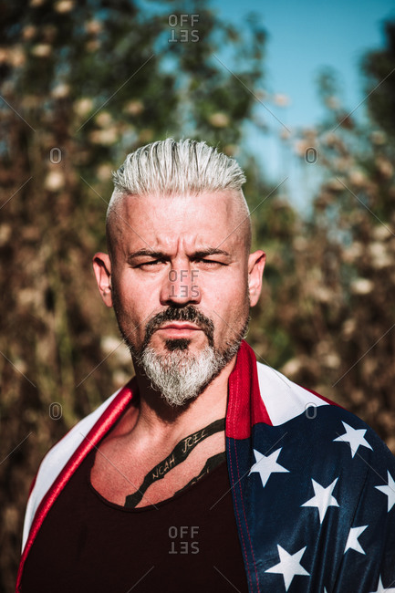 Serious middle aged bearded male with tattoo wrapped in American flag looking at camera while standing against blurred nature