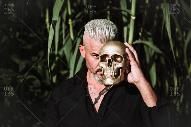 Brutal bearded mature male with tattooed chest holding human skull and looking at camera with challenge while standing against tall green plants