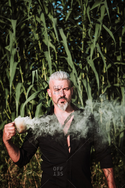 Serious brutal gray haired male with beard and mustache holding smoke bomb and looking at camera while standing against tall corn plants in field