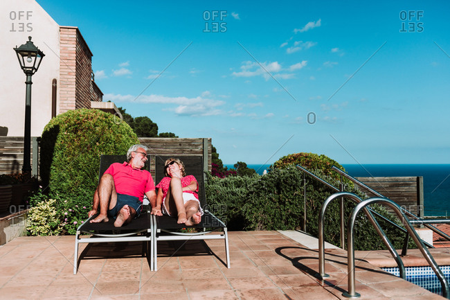Tender elderly couple lying on deck chairs and resting together at resort during summer vacation on sunny day