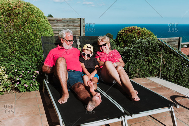 Smiling grandmother and granddad lying on deck chairs together with adorable boy and relaxing during summer weekend